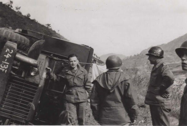 My grandfather's caption reads: Posing before my overturned ambulance, Nov. '51