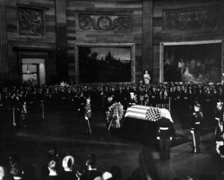 President Lyndon B. Johnson placing a wreath before the flag-draped casket of President Kennedy, during funeral services held in the United States Capitol Rotunda, November 24, 1963.