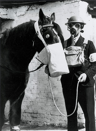 'The West Ham Borough Council Veterinary Department have devised a special gas protection bag for horses, and have instigated a corps of men and 21 dressing stations for any of the borough's 200,000 animals in the time of war. It is a large nose-bag which fits over the horse's head, and is fixed with a zip fastener, the idea being with a little food in the bag the horse would be quiet during an air raid. A long halter is also attached to allow the driver to get to shelter and still have his horse under control. The fetlocks are bandaged with special oil-skin to protect them from mustard gas'.