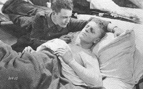 Paul tries to comfort his dying friend in All Quiet on the Western Front (1930).